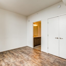 Bedroom with plank flooring and view of bathroom at tellus luxury Arlington apartments