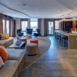 resident lounge with kitchen, countertop seating, social seating, cocktail tables and large windows - luxury apartments near court house metro