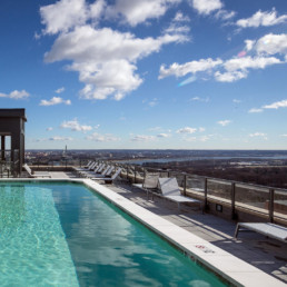 rooftop pool with chaise lounge chairs and view of the city - luxury courthouse va apartments