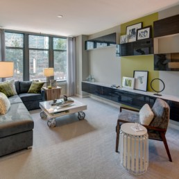 living area with couch, storage cabinets, coffee table, side chair, modern artwork and large windows - arlington va luxury apartments