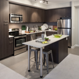 kitchen with island, tile back splash, tile flooring, stainless steel appliances, recycled porcelain countertops, and modern lighting - luxury apartments in arlington va