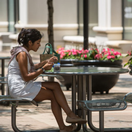 woman having a snack at ouside picnic table near tellus luxury apartments in arlington va