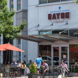 exterior of bayou bakery with people eating in the outdoor seating area near tellus luxury apartments in arlington va
